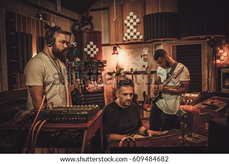 Professional music band recording song in boutique recording studio