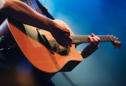 Professional musician plays acoustic guitar solo on concert stage in music hall.Analog audio equipment in close up.Retro style sring musical instrument on rock and roll festival in nightclub.