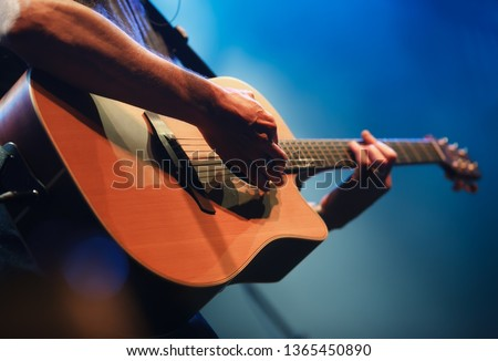 Professional musician plays acoustic guitar solo on concert stage in music hall.Analog audio equipment in close up.Retro style sring musical instrument on rock and roll festival in nightclub. #1365450890