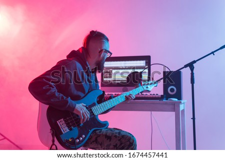 Professional musician recording guitar in digital studio at home, Music production technology concept.