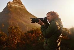 Professional nature wildlife photographer take photos on camera