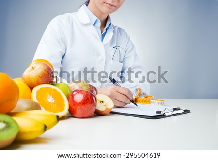 Shutterstock Professional nutritionist working at desk and writing medical records with fresh fruit on foreground