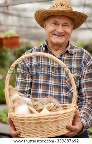 Professional old farmer is presenting a basket of milk and eggs. The man is standing in his garden and smiling. He is looking at camera happily