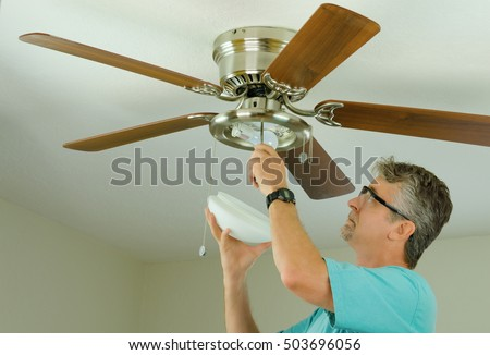 Professional or DIY do-it-yourself home owner doing ceiling fan repair work with the glass cover removed as he adjusts the fixture. #503696056