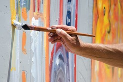 Professional painter at work, painting a street wall