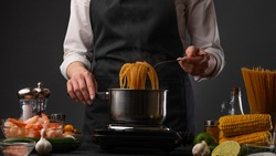 Professional pasta cook with italian pasta with shrimps and vegetables. Chef cooks pasta. Boiling water in a saucepan, gray background, horizontal photo