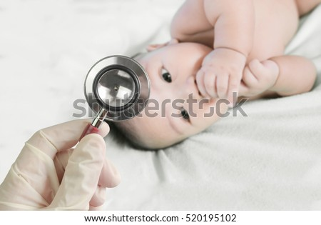 Professional pediatrician examining infant in the hospital. Stethoscope in doctor\'s hand and Blurred background of cute asian baby on the towel.