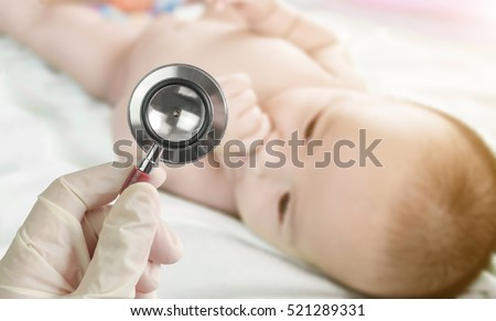 Professional pediatrician examining infant in the hospital. Stethoscope in doctor\'s hand and Blurred background of cute  baby on the towel.