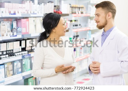 Professional pharmacist helping his female customer choosing products at the drugstore. Beautiful Asian mature woman shopping at the pharmacy talking to a helpful chemist client service friendly