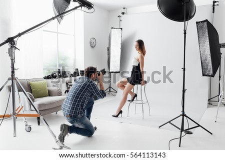 Professional photo shooting at the studio: a beautiful young model is smiling and posing; the photographer is taking pictures with a digital camera
