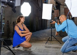Professional photo shooting outdoors. Attractive glad pleasant positive female model posing to photographer on city street