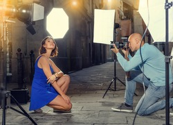 Professional photo shooting outdoors. Attractive positive female model posing to photographer on city street