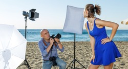 Professional photo shooting outdoors. Man photographer working with young model on sunny seaside