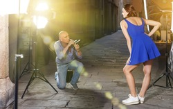 Professional photo shooting outdoors. Professional man photographer working with happy model on city street