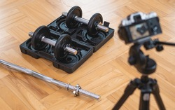 Professional photocamera shoots dumbells and barbell with box they are on floor in living room.