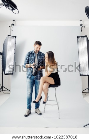 Professional photographer and young beautiful model posing together, the man is showing her picture previews on the camera display #1022587018