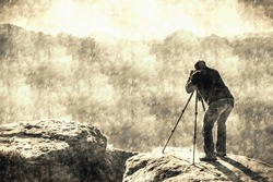 Professional photographer at tripod on cliff and hard working. Dreamy fogy landscape blue misty sunrise in a beautiful valley below Calotype filter. Old photo style.