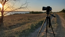 Professional photographer camera on tripod stands at dirt road near bare tree and looks to sunset sun over water. Countryside landscape with camera on stand and nobody