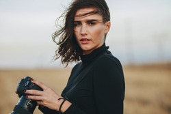 Professional photographer during a outdoors photoshoot. Young woman in casual holding a photo camera outdoors.