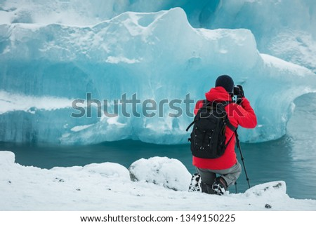 Professional photographer in red coat and black backpack taking picture of glacier ice