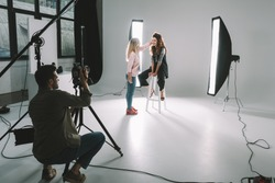 professional photographer, makeup artist and beautiful model on fashion shoot in photo studio with lighting equipment
