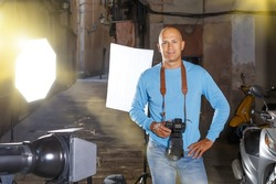 Professional photographer. Portrait of confident adult man holding camera in hands while standing among lighting equipment on city street