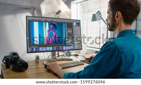 Professional Photographer Sitting at His Desk Uses Desktop Computer in a Photo Studio Retouches. After Photoshoot He Retouches Photographs of Beautiful Female Model in an Image Editing Software Сток-фото ©