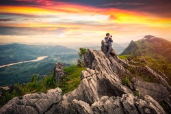 Professional photographer takes photos on the peak of rocks mountain at sunset, success,winner, leadership concept