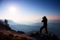 Professional photographer takes photos with mirror camera on peak of rock. Dreamy fogy landscape, spring orange pink misty sunrise in beautiful valley below. Professional photographer.Dreamy landscape