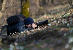 Professional photographer taking picture in nature with a digital camera and telephoto lens