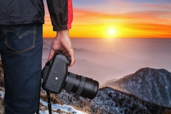 professional photographer with camera at sunset on mountains.