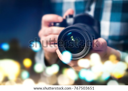Professional photographer with camera. Man taking photos late at night. Photography and paparazzi concept. Abstract bokeh city lights.