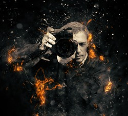 Professional photographer with dslr camera in fire on dark background