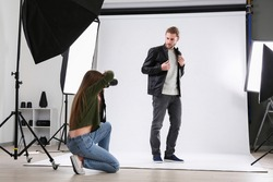 Professional photographer working with model in studio