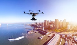 Professional photography drone with the cinema camera flying over San-Francisco pears and the financial district at the summer sunset. Remote control photography innovations concept.