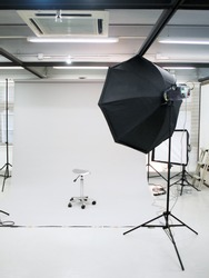 Professional photography studio setup with flash lighting and white background