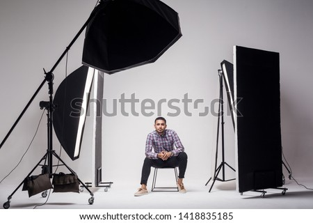 Professional photography studio showing behind the scenes lights. fashion handsome young man model at studio in the light flashes, sitting and looking at camera. indoor studio shot on grey background.