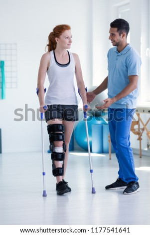 Professional physiotherapist taking care of sportswoman during rehabilitation