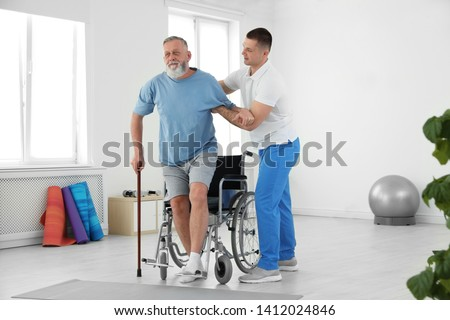 Professional physiotherapist working with senior patient in rehabilitation center ストックフォト ©