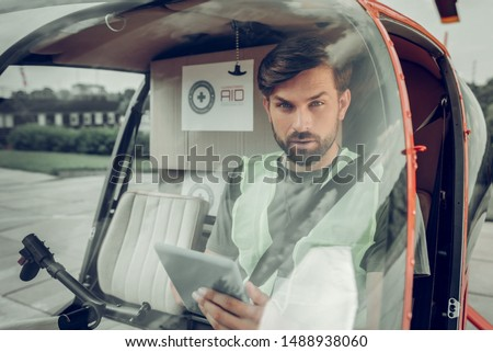 Professional pilot. Professional pilot texting his colleague sitting in helicopter flying with humanitarian help