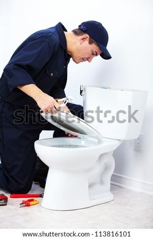 Professional plumber doing toilet reparation. Plumbing repair service.