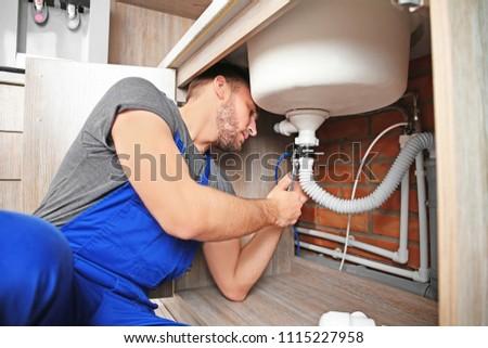 Professional plumber in uniform fixing sink indoors