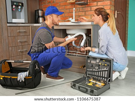Professional plumber with client near kitchen sink