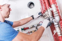 Professional Plumber Work. Caucasian Worker Checking on Water Valves.