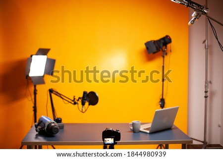 Professional podcast and vlogging setup in studio with yellow background.