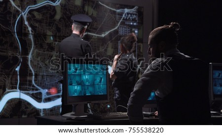 Professional policemen tracing group of bandits in room of video monitoring watching movements on city map while other colleagues working