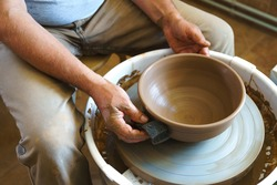 Professional potter working at kick wheel in home studio. Handmade mastery concept. Artisan at workshop.