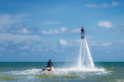 Professional pro fly board rider in tropical sea, water sports concept background. Summer vacation fun outdoor sport.