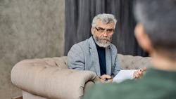 Professional psychoanalyst listening to depressed caucasian man during appointment in office, selective focus. Psychotherapy concept