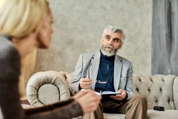 Professional psychoanalyst listening to depressed young caucasian woman during appointment in office, selective focus. Psychotherapy concept